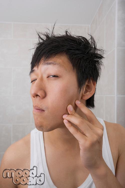 Asian mid adult man examining his face in bathroom
