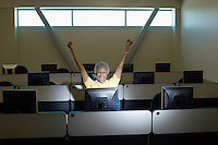 Mature female student celebrating in computer classroom
