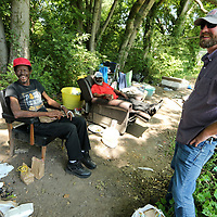 Perry Burkart talks with Tupelo homeless residents Michael Neal and Robert Cayson at their camp on Thursday.