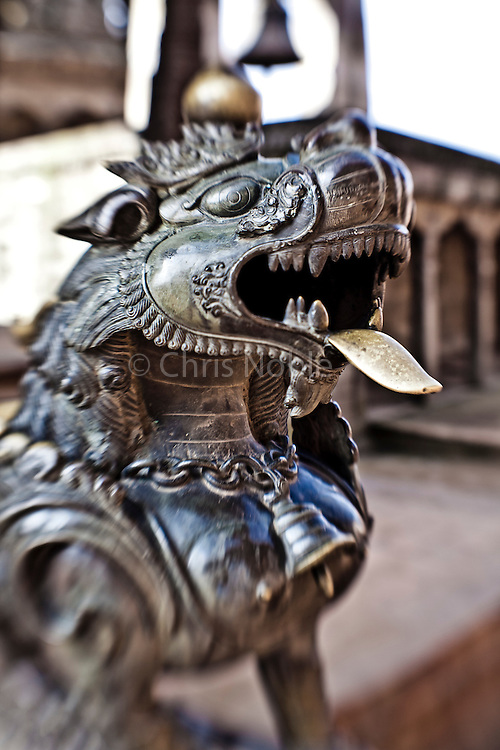 A lion statue guards a temple entrance in Bhaktapur's Durbar Square.