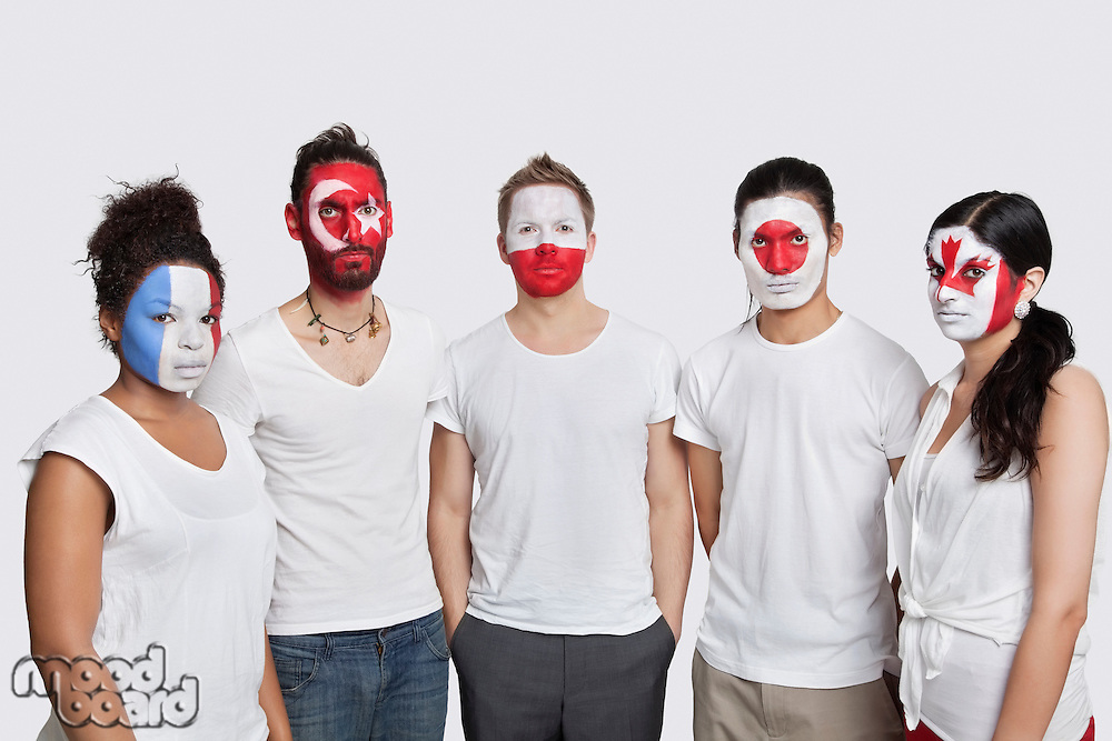 Portrait of serious Multi-ethnic group of friends with various national flags painted on their faces standing against white background