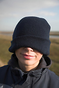 Teenage boy with woollen hat pulled down over his face in outdoors rural location, UK