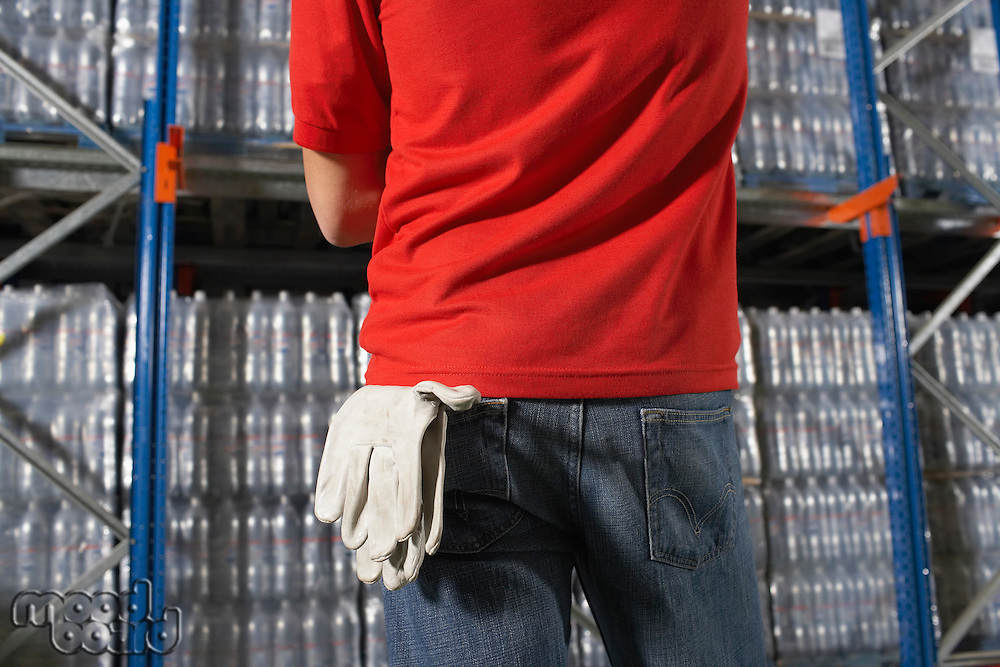Warehouse Worker standing in front of full shelves gloves hanging from back pocket mid section rear view