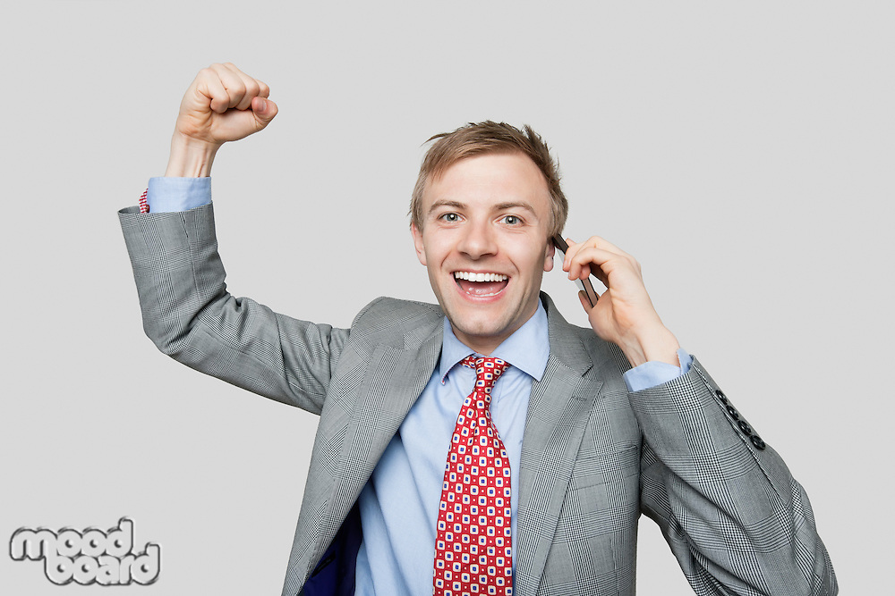 Portrait of handsome businessman with clenched fist talking on cell phone over colored background