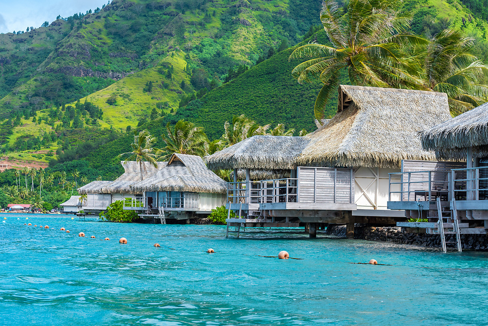 Thatched roof houses on a lagoon in Moorea Island in the South Pacific. Green mountains in the background.
