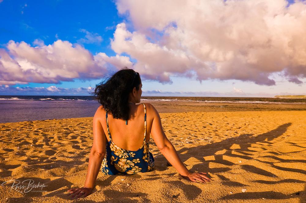 Woman enjoying the sunset at Tunnels Beach, North Shore, Island of Kauai, Hawaii