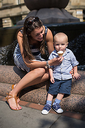 © Licensed to London News Pictures . 05/07/2013 . Manchester , UK . Mum Melissa Ratcliffe (30 from Ramsbottom) gives her son Harry Ratcliffe (18 months) an ice cream by fountains in Manchester City Centre's St Anne's Square . People enjoy the sunshine weather in Manchester City Centre . Photo credit : Joel Goodman/LNP