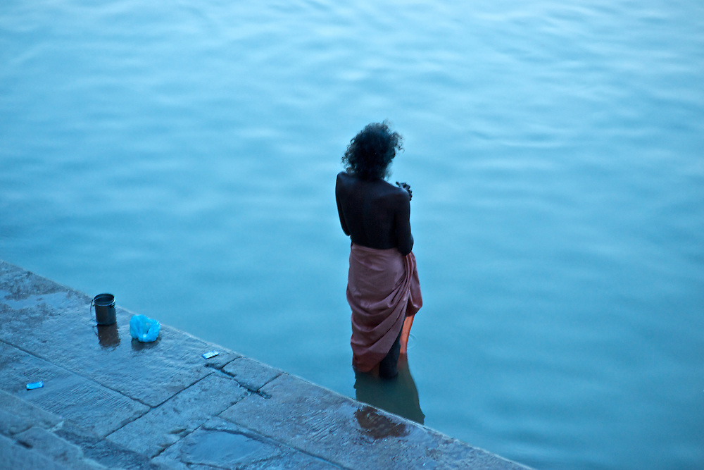 This man was standing just along the edge of the ghats along the Ganges River.  Normally crowded, he found a few silent moments.  The Ganges normally appears brown and muddied, it's quite polluted, but in the pre-dawn hours it appears a beautiful turquoise.