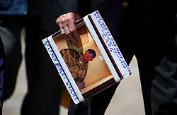 © Licensed to London News Pictures. 06/07/2016. London, UK. A picture of  Gunner Stephen Wright being carried by a member of his family outside the QE2 conference centre in London where the long-awaited Chilcot inquiry into the war in Iraq has been released. Photo credit: Ben Cawthra/LNP
