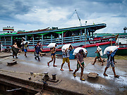 22 NOVEMBER 2017 - YANGON, MYANMAR: Stevedores unload a shipment of rice from a small barge (in the background) docked on the Twante Canal in Yangon. Myanmar's road system lags behind its neighbors in Southeast Asia and a lot of cargo is still moved by ships and barges. From here, export quality rice will be repackaged and shipped overseas and rice for domestic consumption will be shipped to other cities in Myanmar.    PHOTO BY JACK KURTZ