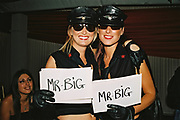 Two women wearing sunglasses, black leather caps and uniforms holding signs which read 'Mr Big', Posh at Addington Palace, UK, August, 2004