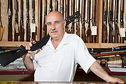 Portrait of a mature man with rifle on shoulder in gun store