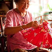 Ms. Zhu folds a traditional cloth and bamboo umbrella at Guangdexing Paper Umbrella Shop, Meinong Township, Kaohsiung County, Taiwan