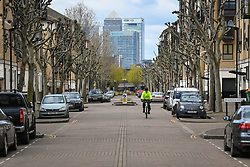A cyclist rides on empty streets within sight of Canary Wharf, in east London, as the UK continues in lockdown to help curb the spread of the coronavirus.