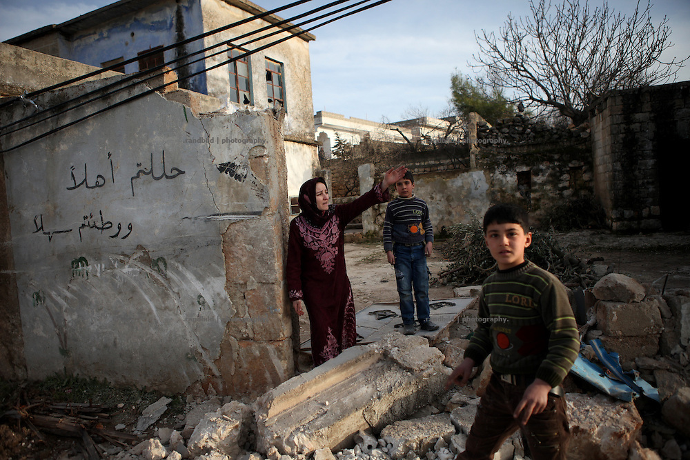 """A woman stand on her property destroyed by syrian troops. The arabic words written on the wall mean """"welcome"""", which is common to write on the wall, when someone return from mekka. On 22. February the syrian army attacked the village of Kureen, Province of Idlib, Syria. Kureen was among the first villages in the northwest of Syria controlled by the opposition. Some villagers and members of the defence units escaped to surrounding olive orchards, when the attack begun in the early morning. A majority of the inhabitants didn´t manage to escape. The heavy shelling lasts 7 houres. Soldiers searched all houses, burnt some of them down, loote shops, stole cars and furniture. About 60 motorcycles were burnt down. Tanks demolished several houses. 6 men were executed. One woman died as a result of an heart attack."""