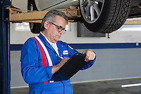 Mechanic writing on clipboard