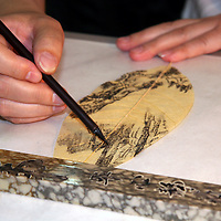 Asia, China, Kunming. Chinese rrtist paints on leaf.