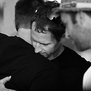 Nigel Wilson, who organized the event, hugs Buck Rowlee before the paddle-out in memory of Molly Rowlee, at Wrightsville Beach, NC. The event also helped support the Molly Fund  a non-profit dedicated to helping children with lymphoma and their families.