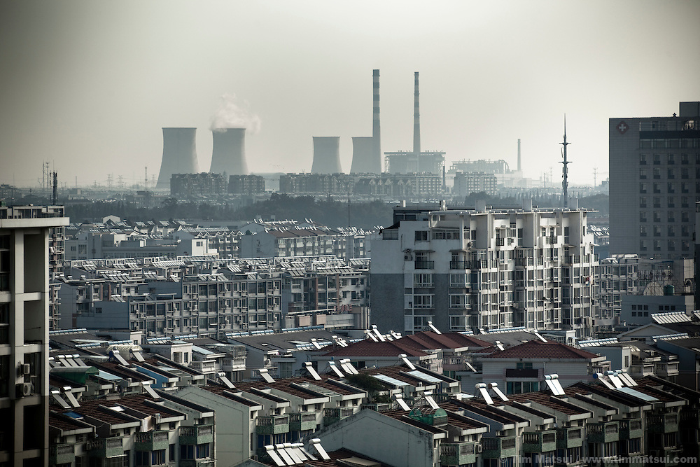 "A coal-fired power plant rises over apartment blocks in the ""New City,"" part of the expansion of Yangzhou, China, a suburb city of Shanghai and major producer of photovoltaic cells for the renewable energy solar power industry."