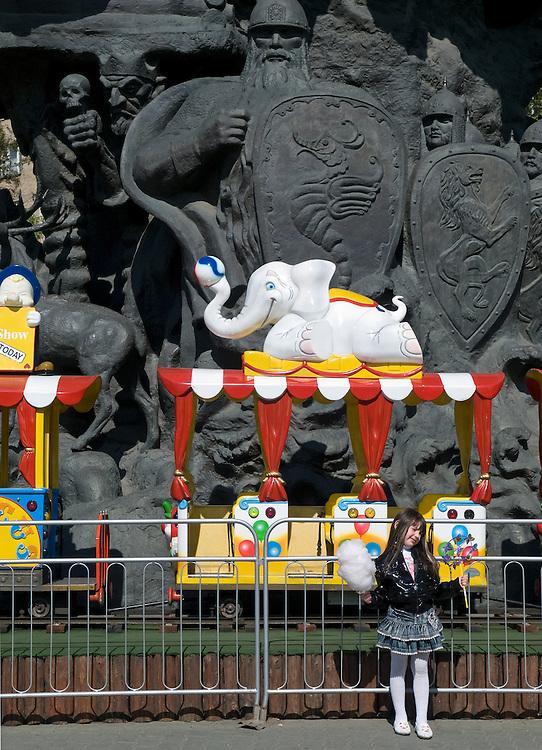 """Mädchen mit Zuckerwatte vor einem Spielzug und monumentalen Skulpturen. Der Moskauer Zoo wurde 1864 eröffnet und ist damit der älteste Zoo Russlands. Hier werden rund 1000 Tierarten mit über 6.500 Exemplaren, vom Rotwolf über den Zobel bis zu den Elefanten, gehalten. Im """"Exotarium"""", einer Art Aquarium, kann man Unterwasserwelten samt Fauna tropischer Meere bewundern. Der Zoo wurde von 1990 bis 1997 grundlegend modernisiert und auf seine heutige Fläche von rund 21,5 Hektar erweitert.<br /> <br /> Inner zone of the Moscow Zoo. The Moscow Zoo is the largest and oldest zoo in Russia - It was founded in 1864."""