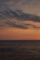 Orange colored sky and clouds over the Pacific Ocean just after sunrise. Image 3 of 10 for a wide-angle panorama taken with a Fuji X-T1 camera and 35 mm f/1.4 lens  (ISO 200, 35 mm, f/16, 1/250 sec). Raw images processed with Capture One Pro and stitched together with AutoPano Giga Pro.