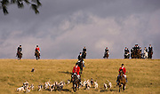 Ivan Dowling, Huntsman for Mr. Stewart's Cheshire Foxhounds, center, leads his pack of hounds across a field near West Grove, Pa. (Photography by Jim Graham)
