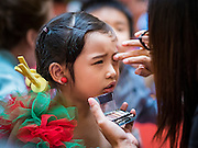 17 SEPTEMBER 2015 - BANGKOK, THAILAND:  A participant in the Santa pageant gets help with her makeup at the World Santa Claus Congress. Twenty-six Santa Clauses from around the world are in Bangkok for the first World Santa Claus Congress. The World Santa Claus Congress has been an annual event in Denmark since 1957. This year's event, hosted by Snow Town, a theme park with a winter and snow theme, hosted the event. There were Santas from Japan, Hong Kong, the US, Canada, Germany, France and Denmark. They presented gifts to Thai children and judged a Santa pageant. Thailand, a Buddhist country, does not celebrate the religious aspects of Christmas, but Thais do celebrate the commercial aspects of the holiday.   PHOTO BY JACK KURTZ