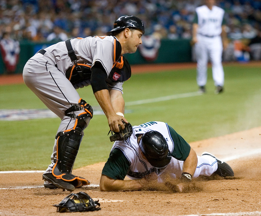 Tampa Bay Devil Rays' Ty Wigginton (R) is tagged out at the plate by the Baltimore Orioles' Ramon Hernandez (L) during the seventh inning of their American League game in St. Petersburg, Florida on April 10, 2006. REUTERS/Scott Audette