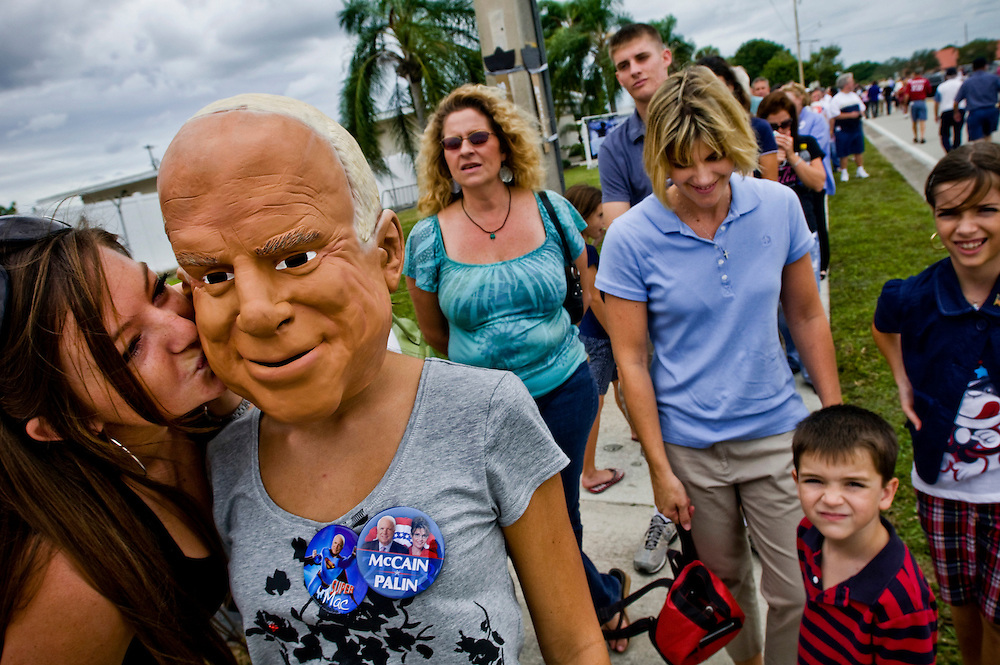 Florida Swingstate..McCain supporters waiting in line to attend a rally where John McCain speaks..Alyssa Salerno, 18, wearing a McCain mask being kissed by her friend..Photographer: Chris Maluszynski /MOMENT