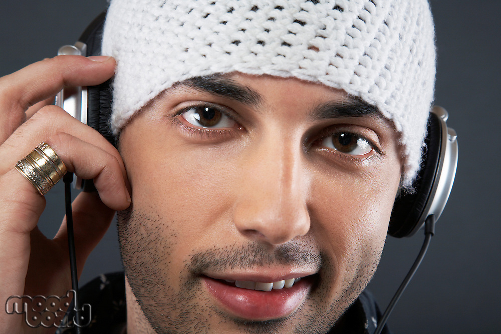 Young man wearing cap and headphones portrait close-up