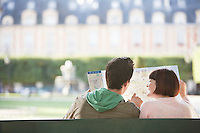 Young couple sitting on bench looking at map in park back view