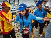 "23 JUNE 2015 - MAHACHAI, SAMUT SAKHON, THAILAND: People get off a fishing boat during the procession for the City Pillar Shrine in Mahachai. The Chaopho Lak Mueang Procession (City Pillar Shrine Procession) is a religious festival that takes place in June in front of city hall in Mahachai. The ""Chaopho Lak Mueang"" is  placed on a fishing boat and taken across the Tha Chin River from Talat Maha Chai to Tha Chalom in the area of Wat Suwannaram and then paraded through the community before returning to the temple in Mahachai.   PHOTO BY JACK KURTZ"
