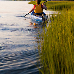 A woman kayaks in a marshy section of the Connecticut River in Old Lyme, Connecticut.  Near Great Island and the mouth of the river.