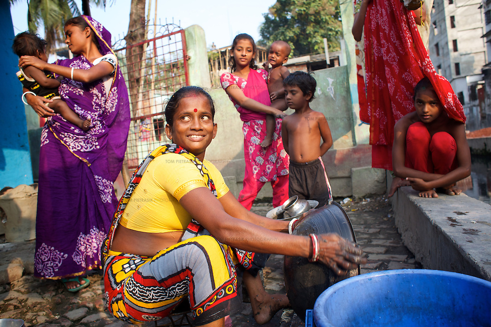 Munni cleans cooking utensils beside a drain close to her home in Horijon Polli. <br />