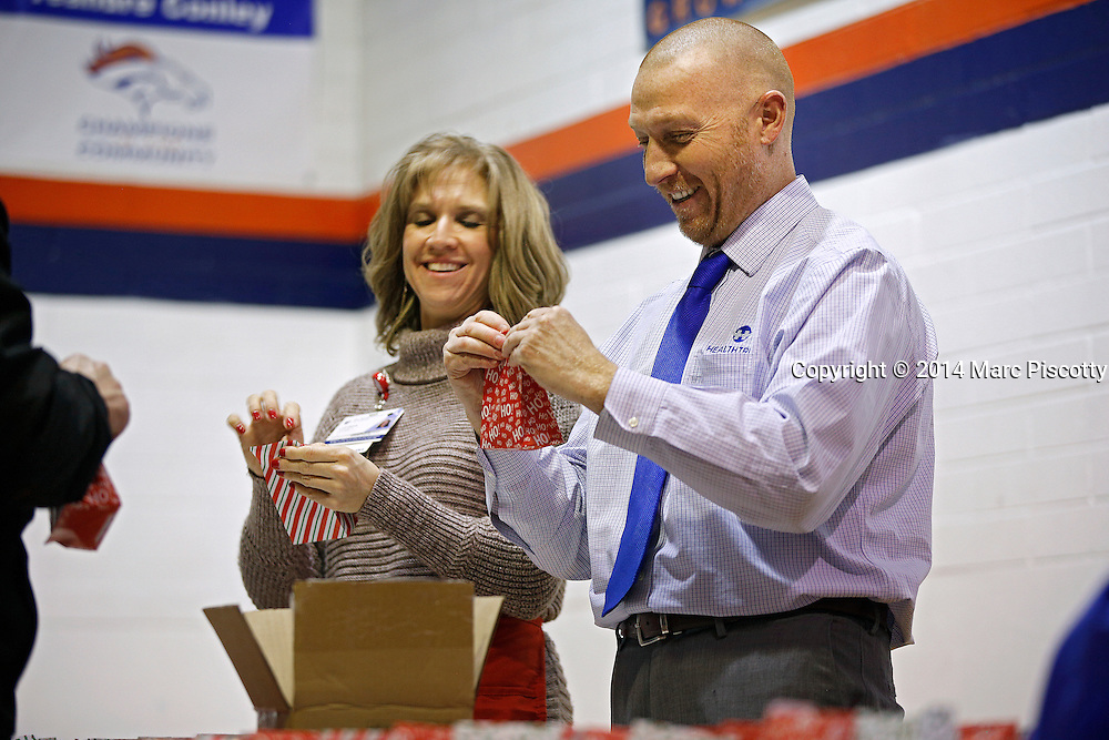 SHOT 12/15/14 5:27:40 PM - Medical Center of Aurora Executive Team members and Directors volunteered their time serving dinner and handing out gifts and toys at the Denver Broncos Boys & Girls Club in Montbello Monday evening. (Photo by Marc Piscotty / © 2014)