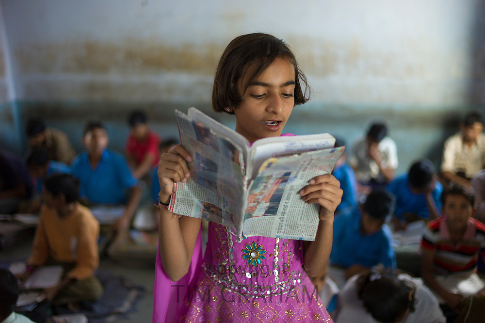 Indian girl reading aloud during English lesson at Rajyakaiya School in Narlai village, Rajasthan, Northern India