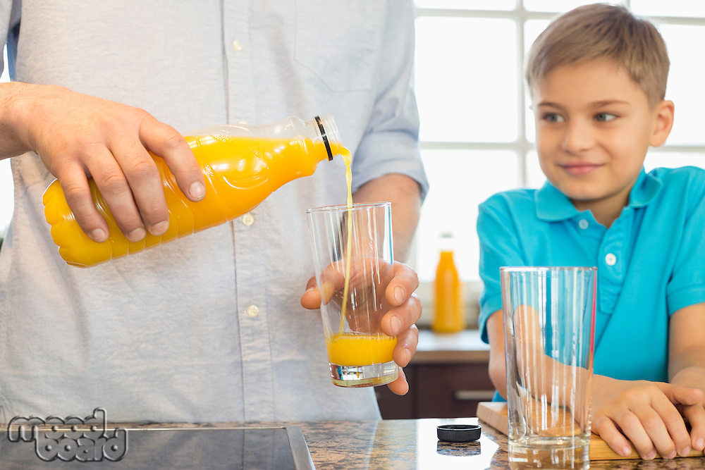Midsection of father serving orange juice for son in kitchen