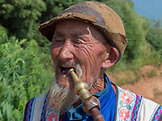 Local Yi mature man smoking a pipe at a small village in the mountains in the Honghe Prefecture, Yuanyang County, Yunnan, China.