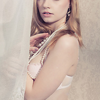 close up of delicate red head young adult wearing a pearl necklace next to a white curtain looking at camera seductively