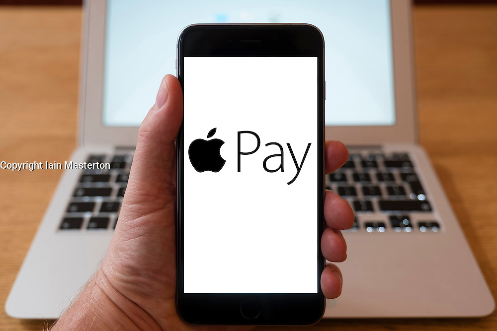 Using iPhone smartphone to display logo of Apple Pay, the  mobile payment and digital wallet service by Apple Inc