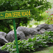 "7/3/11 -- Rt 129 , Maine. Nancy and Jim Bailey keep 7 John Deeres working on their property on Rt 129. With over 20 acres to mow and maintain, it takes all of them -- and one non-Deere machine to keep it clean and well kept. "" Some people play golf, ""  said Nancy.  ""We mow."" It takes 2-3 days each week the retired couple to mow the grass and maintain the property, left to Nancy by her father, O.M. Holmes, who expanded his lawns every year after his retirement from the construction business. ..A stretch of the road not often traveled. Spanning communities, classes and styles ~ of farmers and fishermen, retired and plugging, the elite and working waterfront. (This area has huge potential for great photojournalism).  Photo by Roger S. Duncan."