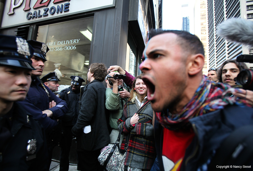 A protester challenges a police officer for not allowing him to pass during a march in the financial  district,on the six month anniversary of the Occupy Wall Street movement.