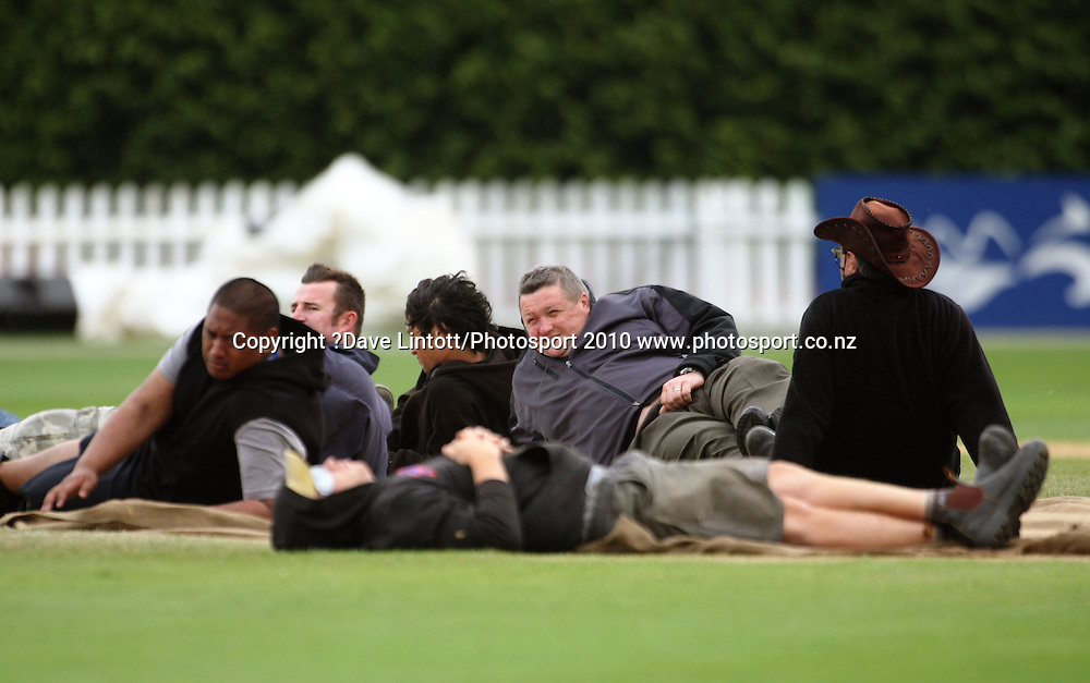 Staff lay on the coversheet to prevent the wind blowing it away.<br /> 1st cricket test match - New Zealand Black Caps v Australia, day four at the Basin Reserve, Wellington. Monday, 21 March 2010. Photo: Dave Lintott/PHOTOSPORT
