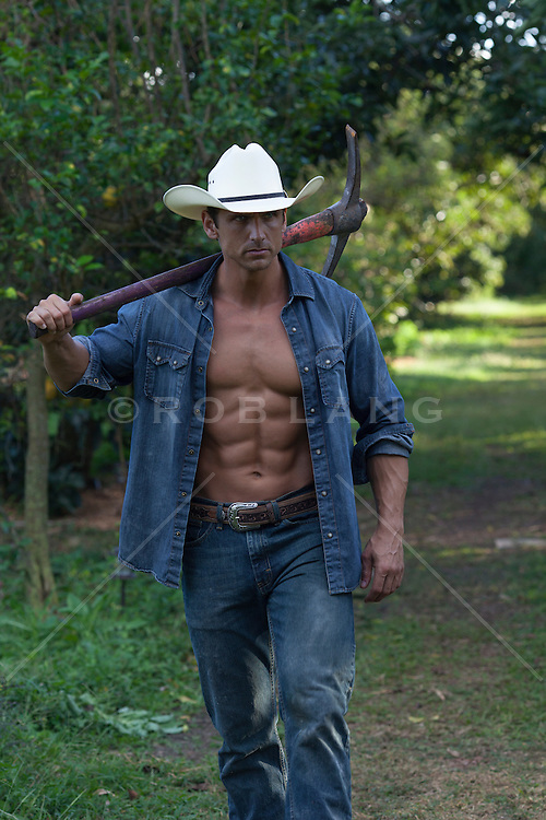 masculine muscular cowboy walking in a field<br />