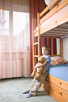 5 year old boy leans on bunk bed holding teddybear