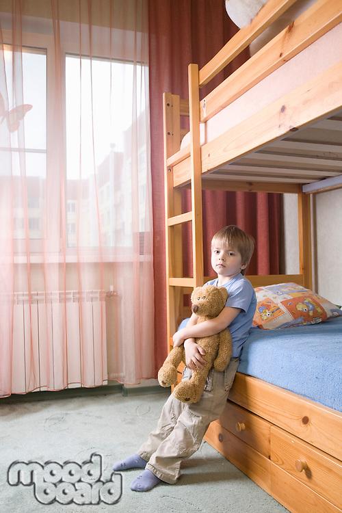 5 year old boy leans on bunk bed holding teddybear