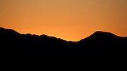 Orange sunset behind a dark ridge in Saguaro National Park, near Tucson, Arizona.