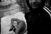 SYRACUSE, NY – NOVEMBER 27, 2010: Ram Khatiwoda (age 11), Arjun Karki (15) play in the first snowfall in Syracuse's North Side and outside their home. As Nepali refugees, the children moved into the area with their family three months earlier.