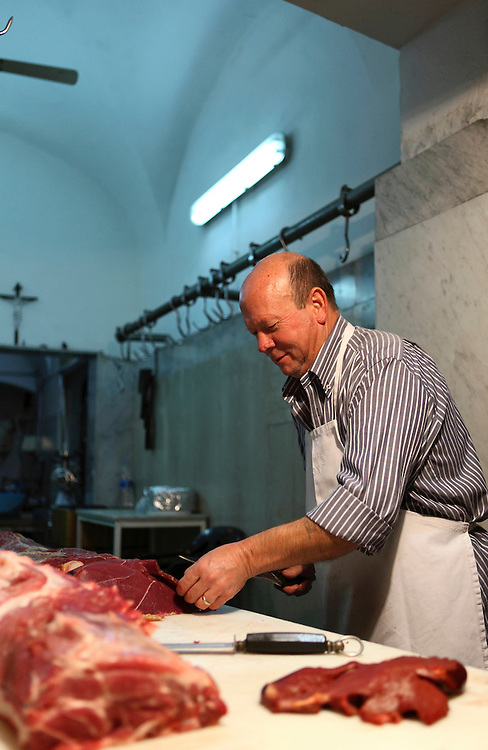 Catania, Sicily. Salvatore Leone is the owner of a small equine butcher shop. He has learned the trade from his father 40 years ago. The butcher is cutting the horse meat for the grill.
