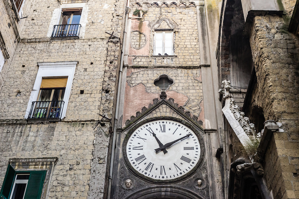 A wall clock adorns a building in Naples, Italy
